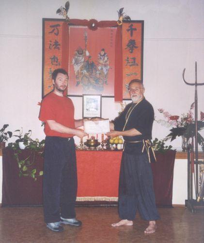 """Sifu Ivan Rzounek (Wing Chun, Praha) přijímá """"Certificate of recognition"""" na návštěvě v písecké škole Sifu Huška"""